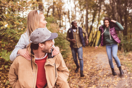 Group of young happy friends piggybacking and having fun in autumn forest