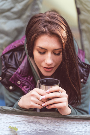 pers: Close-up portrait of beautiful young woman laying in opened tent and holding metallic cup with hot drink Stock Photo