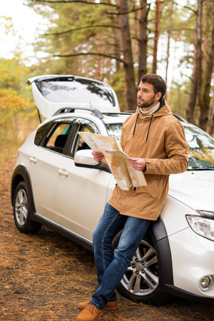 Young bearded man holding map and leaning on white car in autumn forest Stock Photo