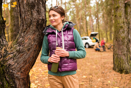 vaso de precipitado: Smiling woman standing with tumbler in autumn forest and father teaching son riding bicycle on background
