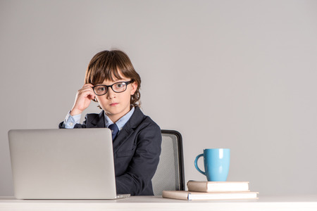 Schoolchild in business suit sitting on desk and looking at camera