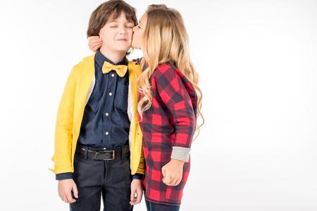 Portret van schoolmeisje knuffelen en kussen in de wang lachende schooljongen op wit