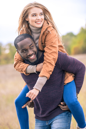 Close-up portrait of happy young couple piggybacking in autumn park Stok Fotoğraf