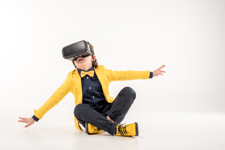 Child in virtual reality headset sitting on grey Stock Photo