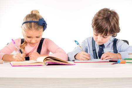 白で隔離のノートブックで宿題を書くの同級生