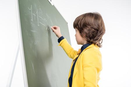 schoolboy: Schoolboy writing with chalk on blackboard
