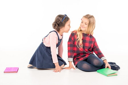 Two schoolgirls sitting with books and talking on white Фото со стока