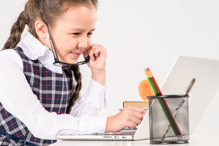 Schoolgirl in glasses sitting at desk with laptop 免版税图像