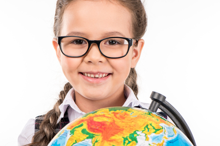 Portrait of schoolgirl smiling at camera with globe in hands isolated on white