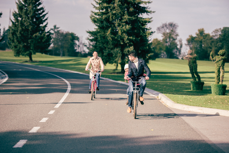 road cycling: Happy family riding bicycles in autumn park, father carrying his adorable little daughter on bike