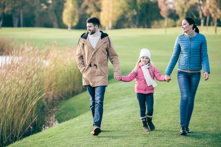 Happy family holding hands and walking near lake in autumn park
