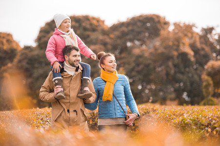 Happy family with one child walking in beautiful autumn park Stock fotó