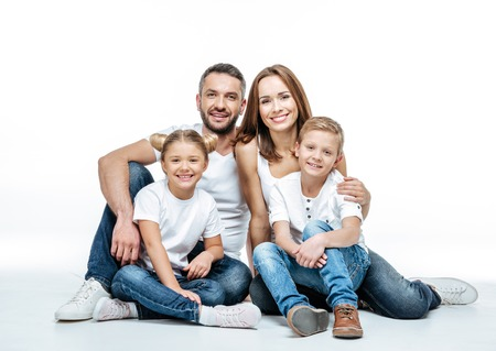 Happy family with two children sitting together and looking at camera isolated on white Stock Photo