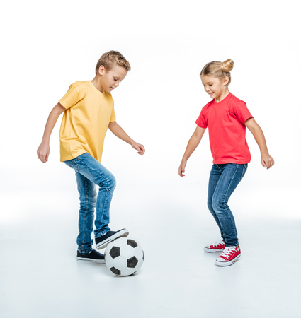 Full length view of Happy siblings in colored t-shirts playing with soccer ball on white