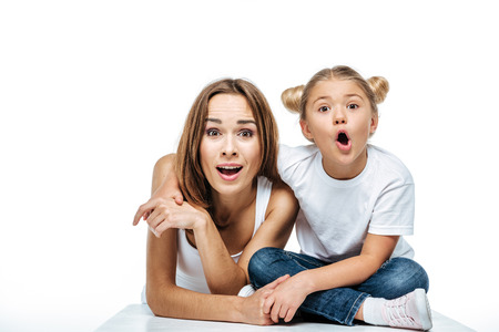 Shocked mother and daughter looking at camera isolated on white Stock Photo