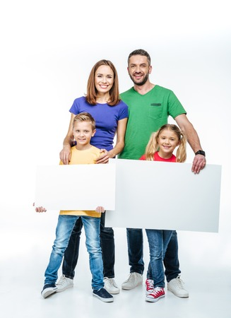 family isolated: Smiling family standing with blank white cards in hands and looking at camera on white
