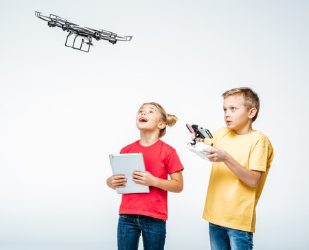 Happy kids using digital tablet and hexacopter drone isolated on white Zdjęcie Seryjne