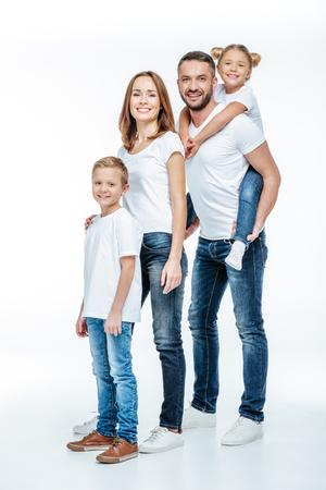 Gelukkige familie in witte t-shirts en jeans die zich verenigt en camera bekijkt die op wit wordt geïsoleerd
