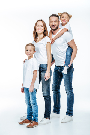 Happy family in white t-shirts and jeans standing together and looking at camera isolated on white Stock Photo