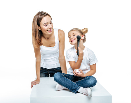 're: Smiling mother looking at adorable little daughter with makeup brush and face powder isolated on white