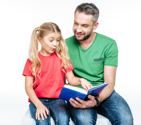 Happy father and daughter sitting and reading book together on white