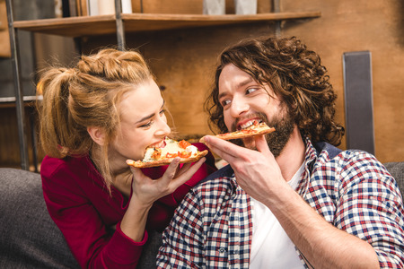 Funny couple eating pizza together