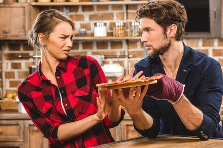 disgusted: Young couple together at kitchen, man showing pizza and girlfriend is disgusted