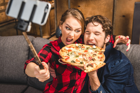 Happy couple taking selfie while eating pizza