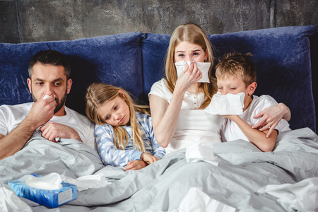 Family of four has a flue and lying on bed together Stock Photo