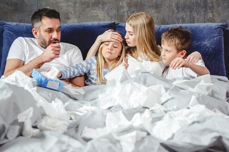 Familie von vier hat einen Kamin und liegt auf dem Bett zusammen