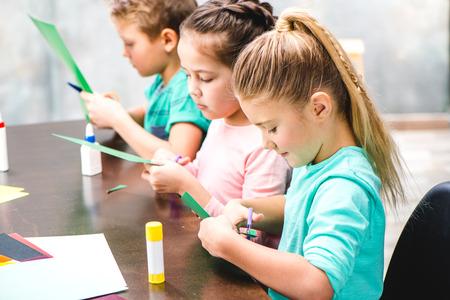 小学生のテーブルに座って、アップリケを作る