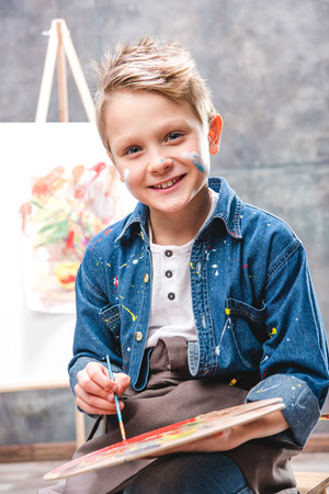 Little male artist painting picture