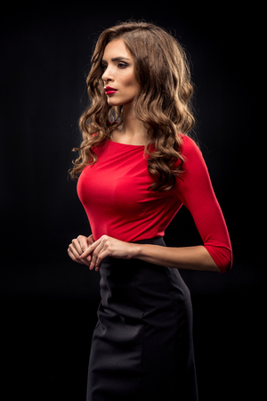 Gorgeous brunette woman with curly hair and stylish makeup posing on black Stok Fotoğraf