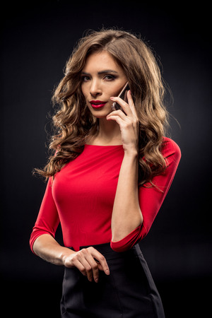 Gorgeous brunette woman with curly hair and stylish makeup talking on smartphone