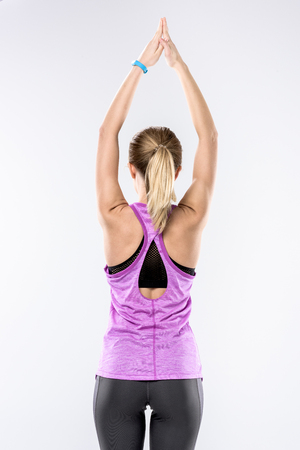 Back view of sporty blonde woman stretching her arms on white Stock Photo