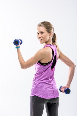 Blonde woman exercising with dumbbells and smiling at camera on white Stock fotó