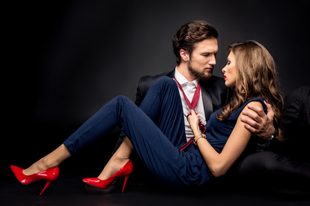 Portrait of beautiful sensual couple in elegant clothes flirting on black