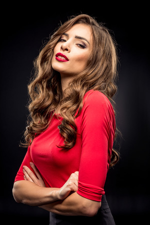 Gorgeous brunette woman with curly hair and stylish makeup looking at camera on black