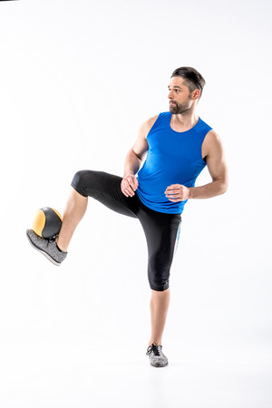 Athletic man in sportswear exercising with ball on white