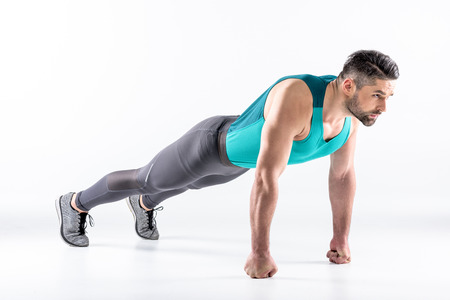 Athletic man in sportswear doing plank exercise on white