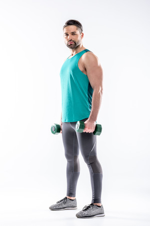 Full length portrait of sporty man exercising with dumbbells  and looking at camera Banco de Imagens