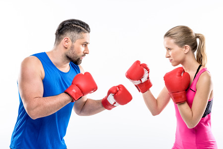 Young man and woman in sportswear boxing looking at each other on white