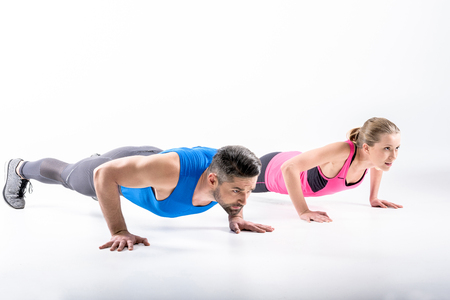 Young sporty couple doing push ups together