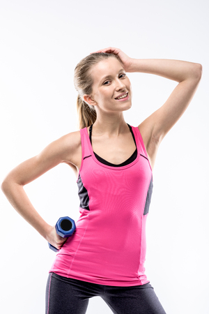 Young woman in sportswear holding dumbbell and posing looking at the camera on white