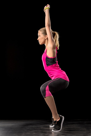 Athletic woman exercising and doing squats on toes