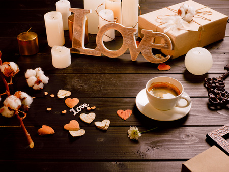 Valentines day composition of wood crafted word love, cup of coffee, present and candles on wooden table