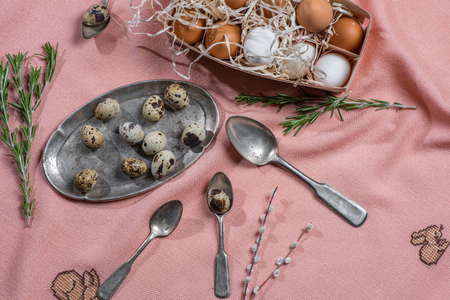catkins: Chicken and quail eggs, catkins, rosemary and old silver cutlery on pink fabric Stock Photo