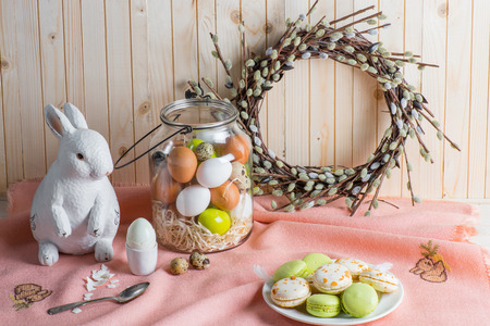Colorful Easter eggs in jar, tasty macarons, catkins wreath and bunny on table