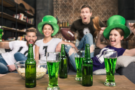 near beer: Green beer in bottles and glasses near friends