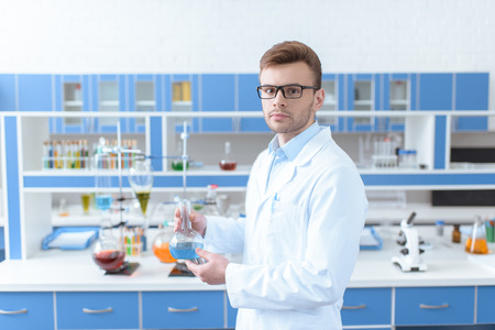 scientist in eyeglasses holding flask with reagent and looking at camera